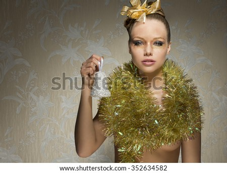 stunning woman with freckles posing in artistic christmas shoot with little bell in the hand, golden ribbon in the hair-style, christmas glossy  make-up and shiny tinsel around neck.