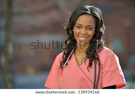 Stunning young African-American female healthcare professional in Pink scrubs shown outside with a stethoscope - stock photo