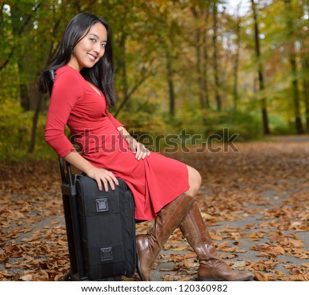 http://thumb9.shutterstock.com/display_pic_with_logo/77601/120360982/stock-photo-stunning-young-asian-woman-in-red-dress-and-boots-sitting-on-a-small-black-suitcase-on-the-side-of-120360982.jpg