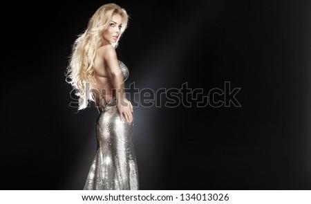 Stunning young beautiful blonde woman wearing silver evening dress posing, looking away. Long curly hair. - stock photo