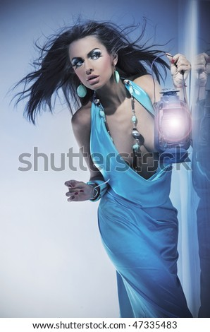Stunning young beauty holding a lantern - stock photo