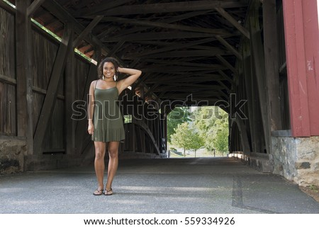 Stunning young biracial woman in green sundress standing in front of covered bridge