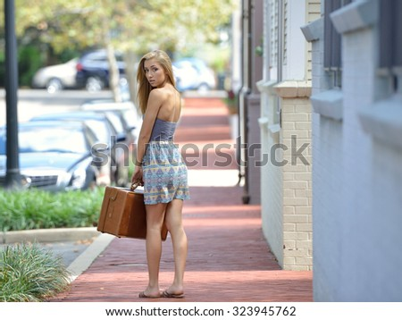 Stunning young blonde woman - in muted sundress stands on city sidewalk holding her vintage suitcase - stock photo