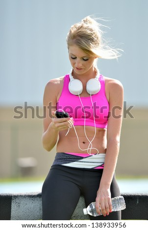Stunning young blonde woman in pink sports bra rests while holding a water bottle and adjusting music on portable music player - stock photo