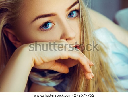 Stunning young blonde woman looking at camera with blue eyes indoors - stock photo