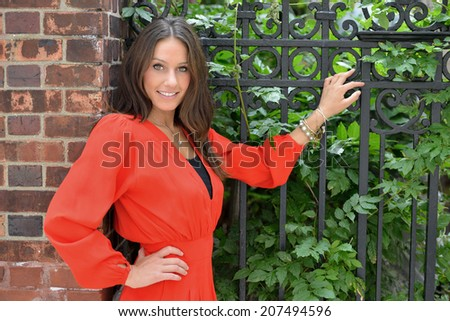 Stunning young brunette female model in red jumper posing outdoors along iron fence - stock photo