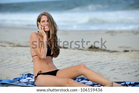 Stunning young Caucasian woman laying on blue beach blanket wearing a black bikini - smiling as she talks on her cell phone - stock photo