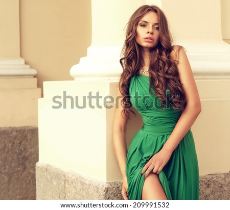 stunning young lady in green dress posing near yellow wall. outdoor fashion portrait - stock photo