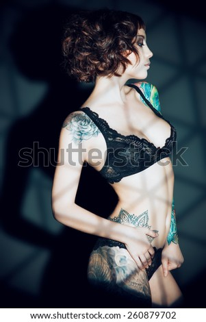 Stunning young woman  alluring in sexual lingerie over dark background. Light and shadow. - stock photo
