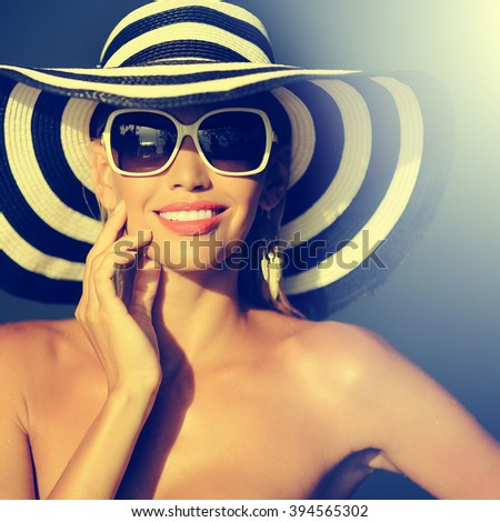 Stunning young woman in elegant hat and sunglasses - stock photo
