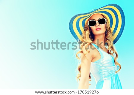 Stunning young woman in elegant hat and sunglasses posing over sky. - stock photo