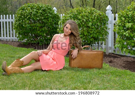 Stunning young woman in peach colored dress and boots sits next to a vintage leather suitcase in grass - travel