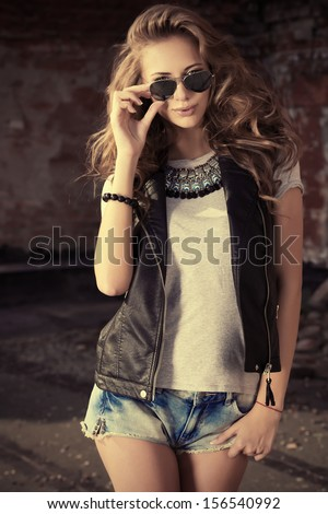 Stunning young woman posing outdoor over brick wall. - stock photo