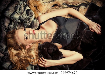 Stunning young woman with beautiful blonde hair lying on furs. Luxury, rich lifestyle. Jewellery. Fashion shot. - stock photo