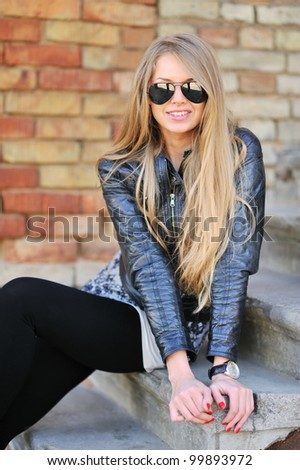 Stunningly beautiful young blond woman in a jacket and aviator sunglasses sitting on the stairs - stock photo