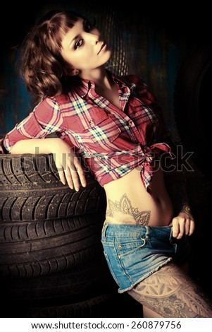 Stunningly sexual young woman posing in the old garage. - stock photo