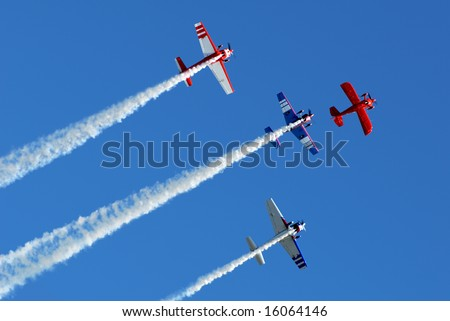Stunt aircraft flying in formation against bright blue sky at air show performance