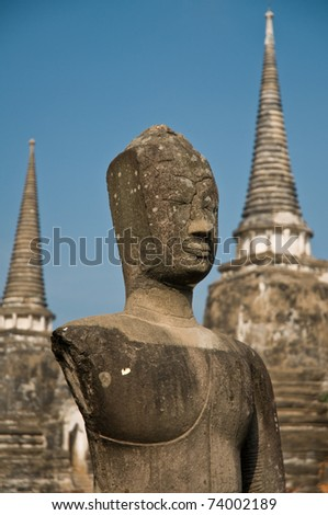 Stupa (chedi) of a Wat in Ayutthaya, Thailand, with Buddha staue. Ayutthaya city is the capital of Ayutthaya province in Thailand. Its historical park is a UNESCO world heritage. - stock photo