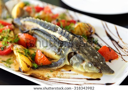 sturgeon baked with greens fruits and vegetables, soft selective focus. - stock photo