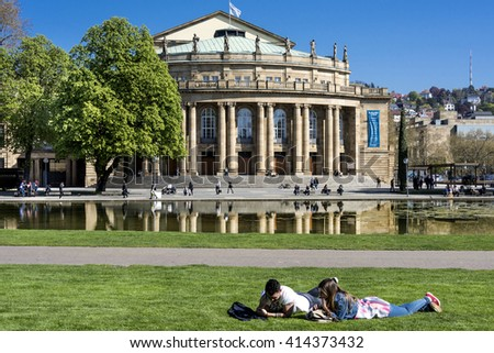 Stuttgart, Germany - April 20, 2016: Young couple relaxes in front of the Opera house in the capital of Baden-Wuerttemberg