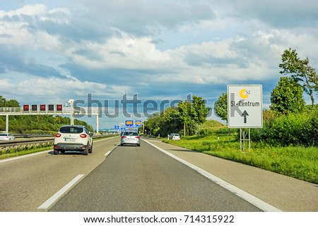 Stuttgart, Germany - August 20, 2017: Sign showing way to SI-Centrum, a mall with musical and casino in Stuttgart-Mohringen, road with cars in front