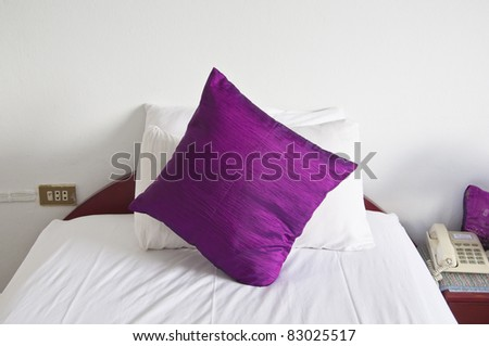 style bedroom interior with single  purple pillows on white wall - stock photo