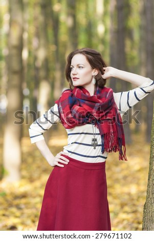 Style Concept: Caucasian Female Model Dressed in Stylish Clothing. Standing Outdoors in Forest. Vertical Image Composition - stock photo