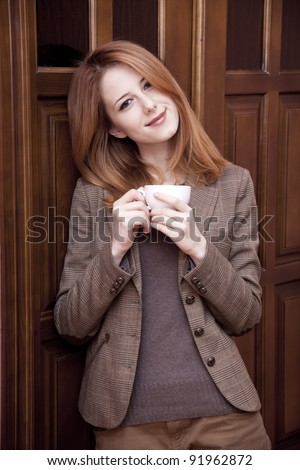 Style redhead girl drinking coffee near wood doors.