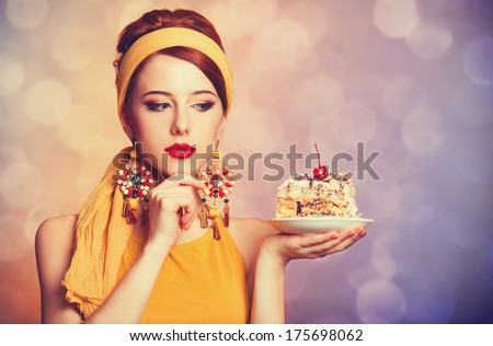 Style redhead girl with cake. Photo with bokeh at background. - stock photo