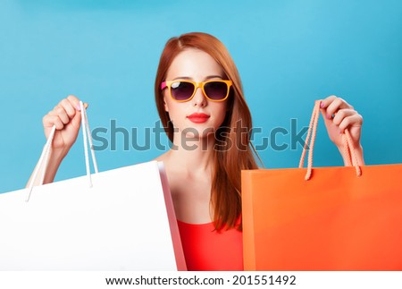 Style redhead women holding shopping bags on blue background. - stock photo