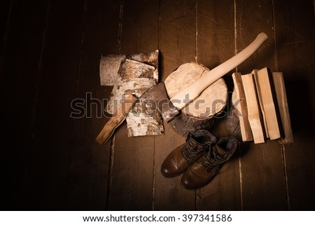 Style woodcutter. Lumberjack. Old woodcutter shoes. Brown shoes with laces. Lumberjack Accessories. Stump, firewood, an ax on a wooden background - stock photo
