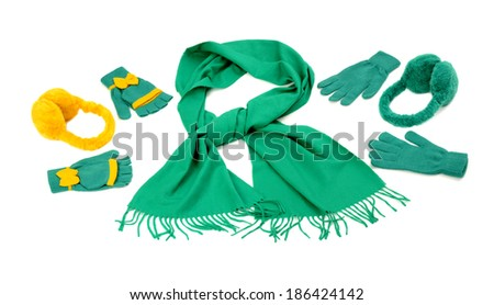 Styling a green scarf with different accessories. Green fringe winter scarf, gloves and earmuffs isolated on white background. - stock photo