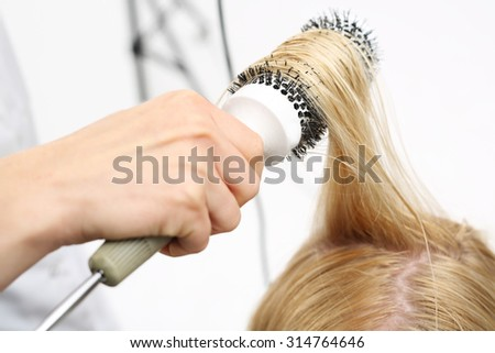 Styling brush.The woman at the hairdresser, barber models hair on a round brush  - stock photo