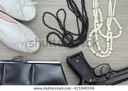 Stylish accessories set for girls and Gun. Women accessories, Still life of fashion, purse, necklace, flat shoes. - stock photo