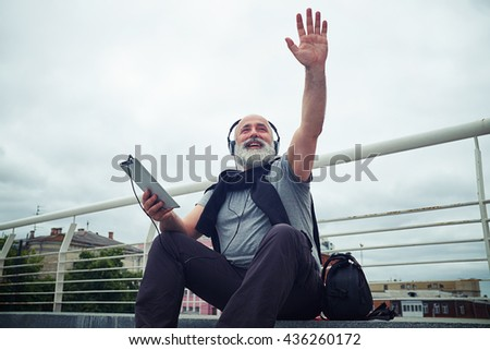 Stylish aged bearded man in casual clothes and headphones is smiling and waving his hand to say Hello while sitting on stairs of the sidewalk - stock photo