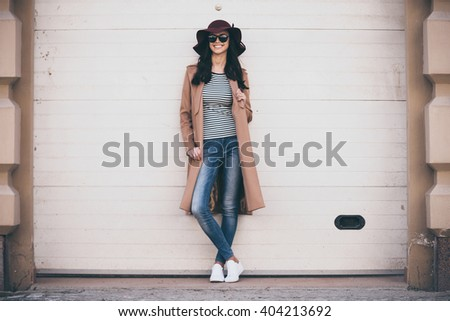 Stylish and cheerful. Full length of beautiful young woman in sunglasses looking at camera with smile while standing outdoors - stock photo