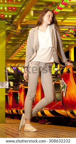 stylish and contemporary portrait. a beautiful young woman riding on the carousel and roller coaster, posing and smiling. clothes in a simple and convenient odezhdu.