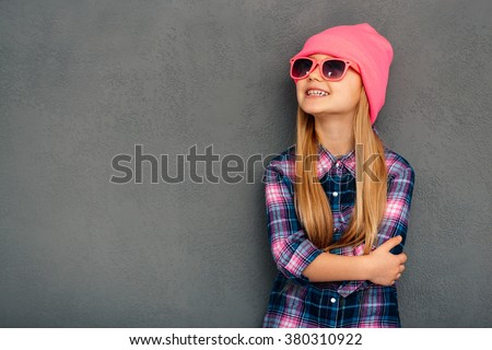 Stylish and cute. Cheerful little girl in sunglasses keeping arms crossed and looking up with smile while standing against grey background