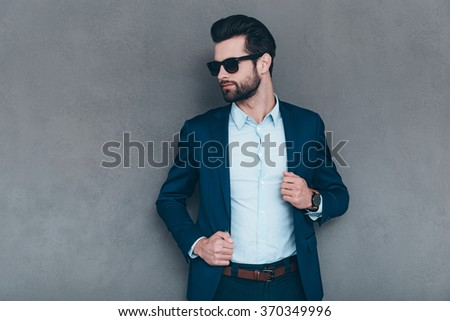 Stylish and successful. Young handsome man in sunglasses keeping hand on his jacket and looking away while standing against grey background - stock photo