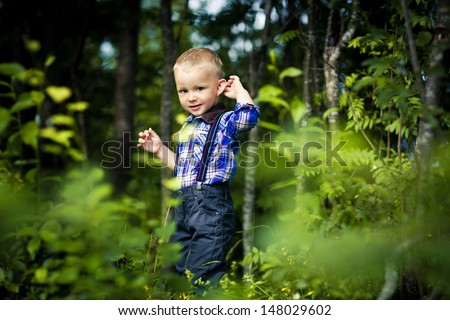 stylish baby boy having fun outside in the park