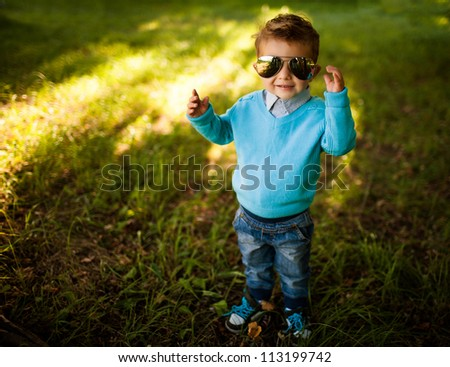 stylish baby boy having fun outside in the park,wearing  glasses - stock photo