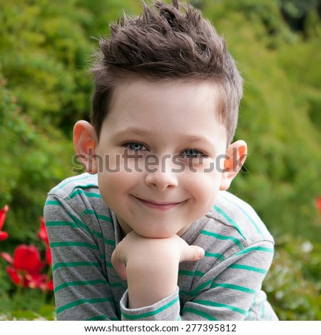 Stylish baby boy with dark hair in  striped polo-neck. Smile. Hipster style. Outdoor shot - stock photo