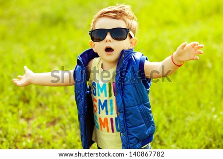 Stylish baby boy with ginger (red) hair in trendy sunglasses and blue jacket standing in the park with hands up and singing a song. Hipster style. Sunny weather. Outdoor shot - stock photo