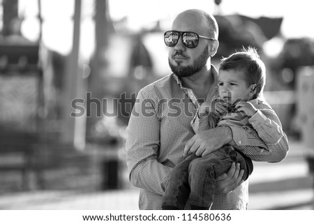 stylish baby boywith stylish father  having fun outside in the amusement Park in sunglasses,black and white - stock photo
