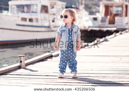 Stylish baby girl wearing denim suit and jacket at wooden pier. Summer season. Child standing outdoors.  - stock photo