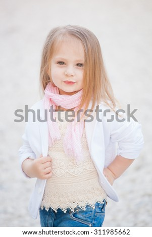 Stylish baby girl with blonde hair outdoors. Little girl 2-3 year old