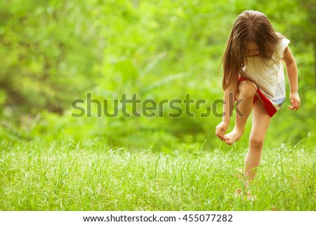 Stylish baby girl with long light brown hair in trendy vintage red and white dress standing in the park and trying to pull of a splinter in foot. Sunny weather. Outdoor shot