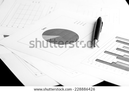 Stylish ballpoint pen lying on a desk on a set of pie and bar graphs in a concept of business analysis, planning and strategy. - stock photo