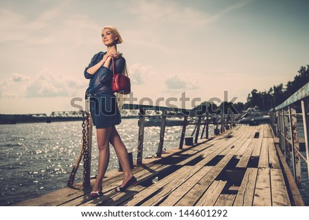 Stylish beautiful blond woman with white scarf and red bag standing near rails of old pier - stock photo