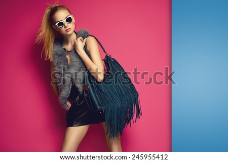 Stylish beautiful blonde woman wearing feather vest holding nice big fringed handbag. Fashion picture